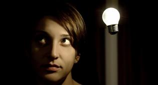 Kuvituskuva: kuvassa nuori nainen, hänen oikealla puolella ylhäällä valaistu hehkulamppu, joka kuvaa idean syntymistä.