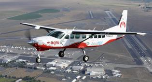 Kuvassa Caravan STC -lentokone lennossa, alhaalla näkyy maisemaa yläperspektiivistä.