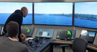 Kaksi merikapteeniopiskelijaa ohjaa laivaa simulaattorissa kohti Suomenlinnan ja Vallisaaren välissä olevaa Kustaanmiekan salmea Helsingissä. Isoista monitoreista näkymä on verrattavissa aluksen tutkien tuottamaan kuvaan konsolitasojen näytöissä.
