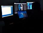 """Merenkulun kyberturvallisuus -julkaisun tummassa kansikuvassa on tietokoneiden näyttöjä, joista heijastuu """"mustahattuhakkerin"""", eli pahansuopaisen verkkorikollisen kuva."""
